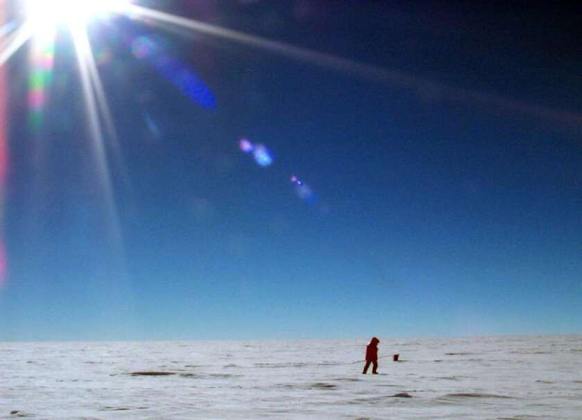 A National Science Foundation researcher trudges across the East Antarctic Ice Sheet. Miles under the ice on which he walks is a freshwater lake as long as Lake Ontario and deep as Lake Tahoe. In a PLOS ONE study, scientists say they have discovered evidence of thousands of different microbes living beneath the surface.