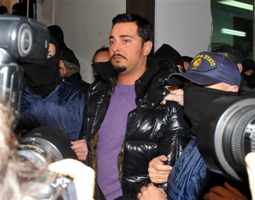 """A man described as Cosa Nostra's No. 2 fugitive boss, identified as Giovanni Nicchi, is held by Italian police officers after his arrest in Palermo, Sicily, southern Italy, Saturday Dec. 5, 2009. Italian Interior Minister Roberto Maroni described convicted Nicchi as a """"young, dangerous, ambitious, pitiless killer."""" Police found the 28-year-old Mafioso, hiding Saturday in an apartment in Palermo. News reports say he tried to flee. (AP Photo/Alessandro Fucarini)"""