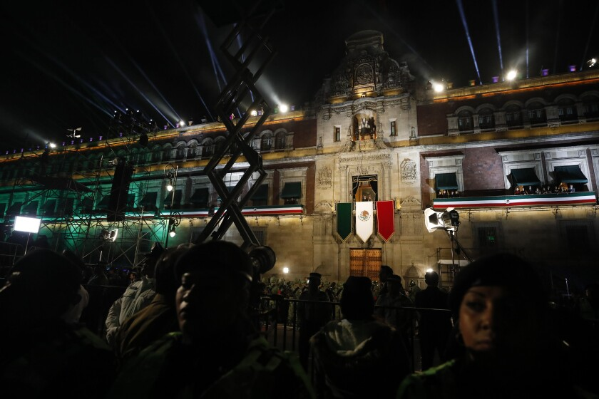 "Police provide a security cordon as President Andres Manuel Lopez Obrador and first lady Beatriz Gutierrez Muller look out toward the crowd from the balcony of the National Palace, after Lopez Obrador gave the annual independence shout to kick of Independence Day celebrations at the Zocalo in Mexico City, Sunday, Sept. 15, 2019. Every year the Mexican president marks the ""Grito de Dolores,"" commemorating the 1810 call to arms by priest Miguel Hidalgo that began the struggle for independence from Spain, achieved in 1821.(AP Photo/Rebecca Blackwell)"