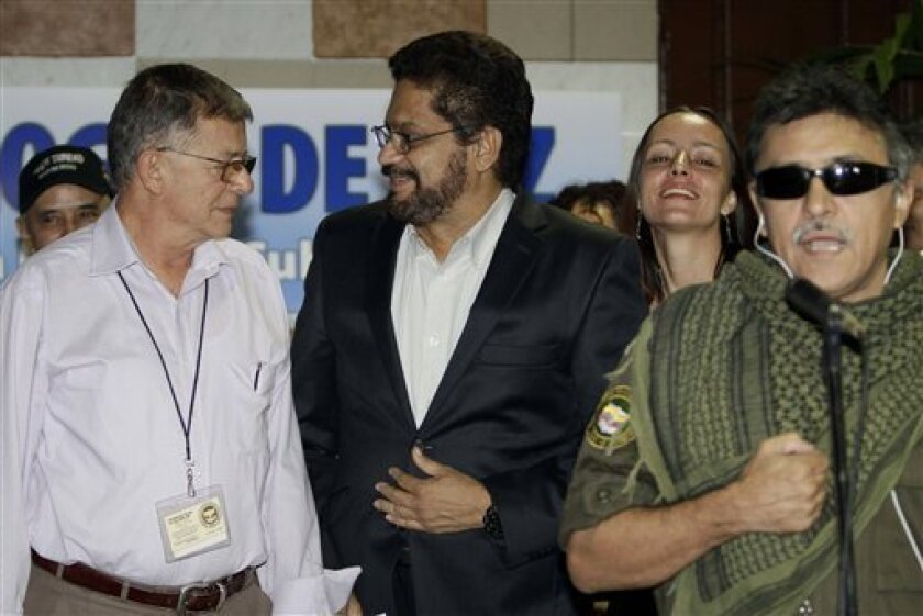 Jesus Santrich, far right, member of the negotiating team for Colombia's Revolutionary Armed Forces of Colombia, or FARC, speaks to journalists during the continuation of peace talks with Colombia's government, as fellow rebel Ivan Marquez, center, who is the chief negotiator, speaks with Ricardo T