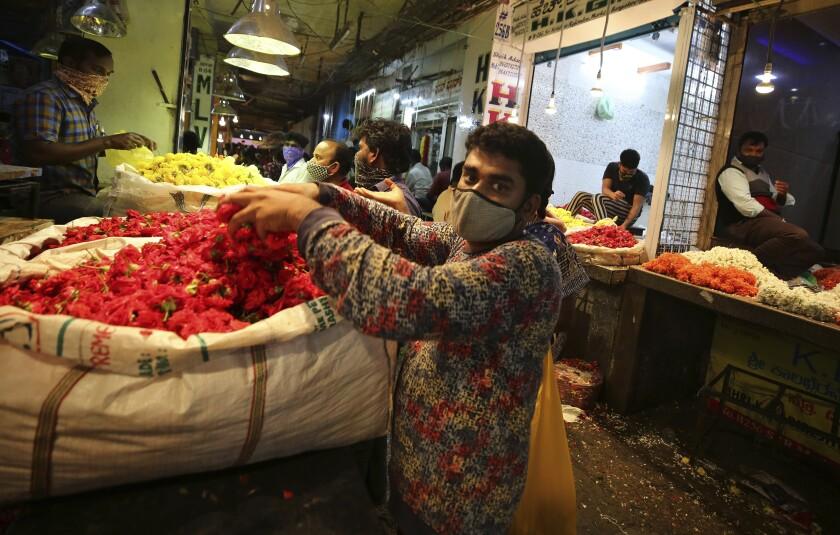 Vendedores colocan flores en un mercado al por mayor antes del festival hindú del Dussehra, en Bengaluru