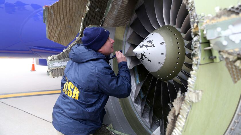 A National Transportation Safety Board investigator examines damage to the CFM turbofan engine on a Southwest plane that had to make an emergency landing in Philadelphia on Tuesday.