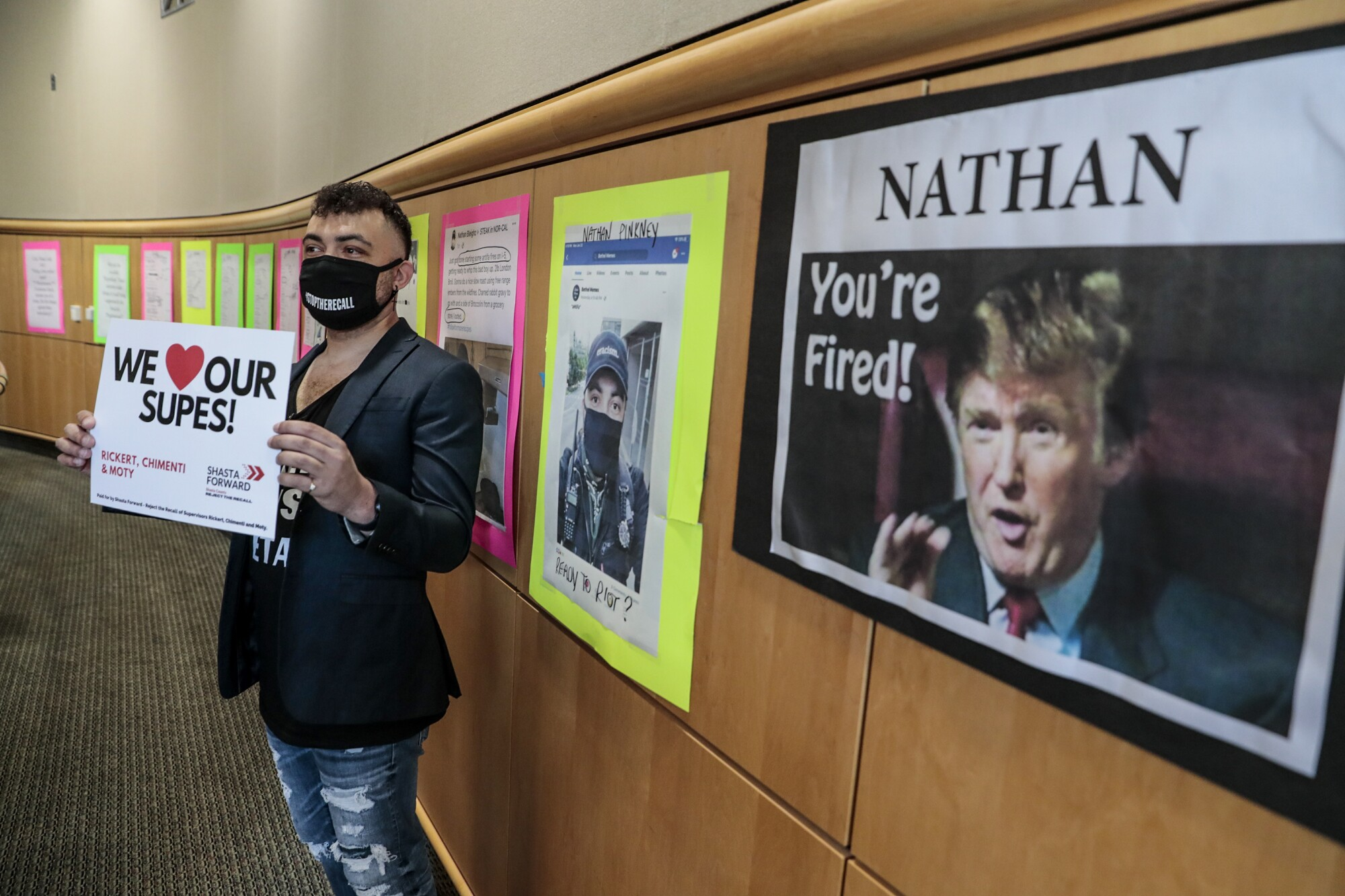 Nathan Pinkney  in front of a wall filled with posters showing his  social media posts and court records