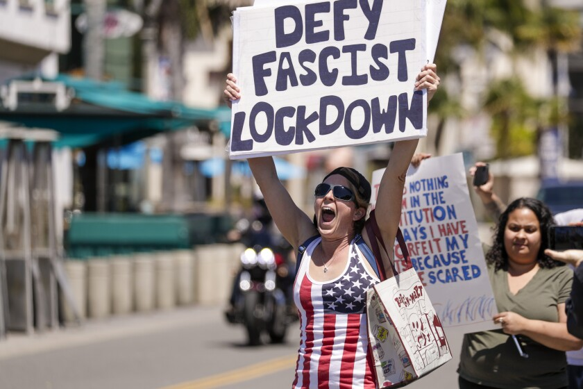 HUNTINGTON BEACH, CA - APRIL 17: Sarah Mason, from Covina, at a rally against the lockdown due to coronavirus pandemic. A big number of Trump supporters rally on Main Street against business closure due to COVID-19 pandemic. Huntington Beach, CA. (Irfan Khan / Los Angeles Times)
