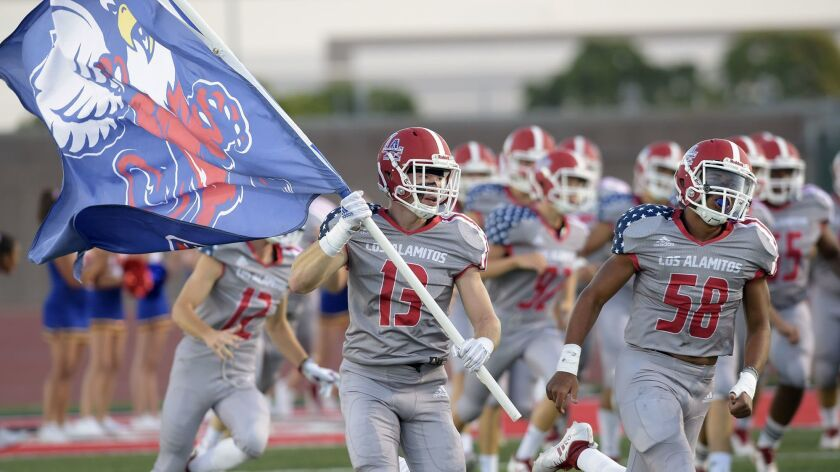 Los Alamitos's Dallas Burke (13) carries the Griffin flag as the team enters the field before the ga