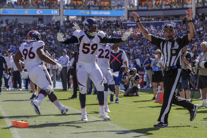 The Broncos' Malik Reed, 59,  looks to the official for a ruling after it appeared as if Chargers running back Austin Ekeler had fumbled at the one-yard line.
