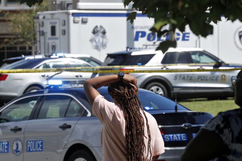 A woman watches as Newport News police officers and Virginia state troopers respond to the scene of a shooting at Heritage High School in Newport News, Va., Monday, Sept. 20, 2021. (Jonathon Gruenke/The Virginian-Pilot via AP)