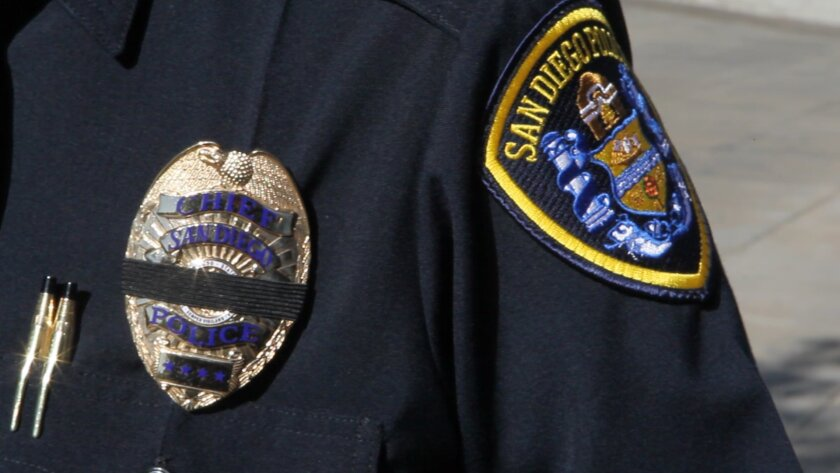 A black band of mourning covers a San Diego Police officer's badge.