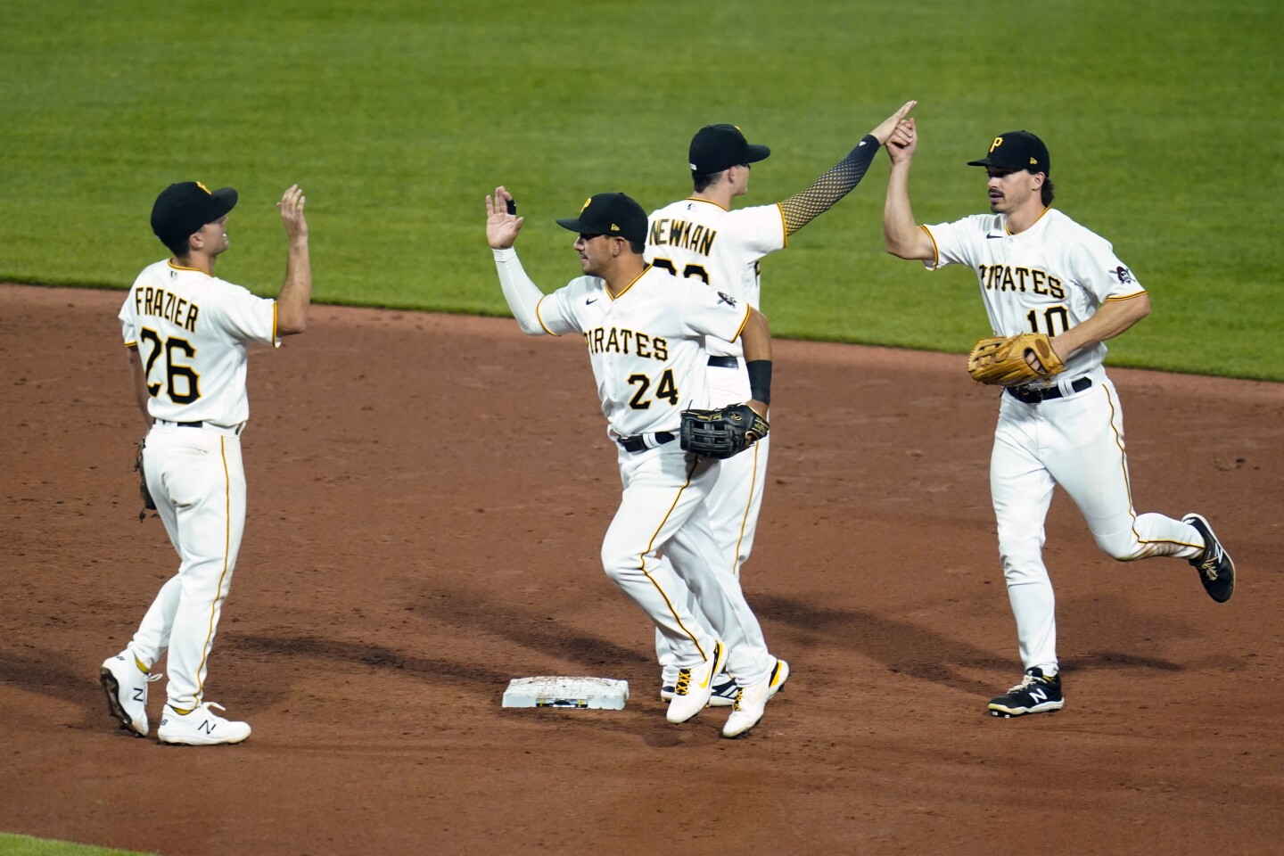 Pittsburgh Pirates' Adam Frazier (26), Phillip Evans (24), Adam Frazier (26), and Bryan Reynolds (10) celebrates after defeating the Kansas City Royals in a baseball game, Tuesday, April 27, 2021, in Pittsburgh. The Pirates won 2-1.(AP Photo/Keith Srakocic)