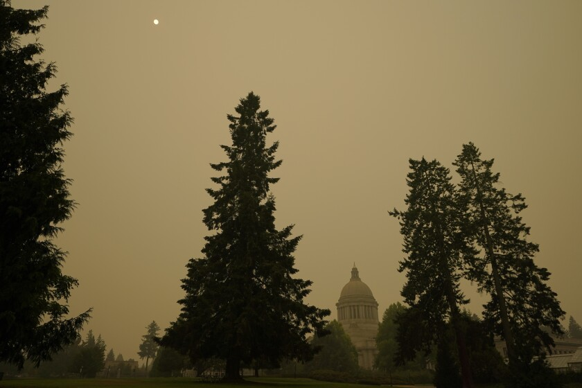 Smoke from wildfires in Oregon and California creates hazy skies as the sun is seen above the Washington state Capitol, Saturday afternoon, Sept. 12, 2020, in Olympia, Wash. Numerous air quality warnings were in place for most of the West through the weekend. (AP Photo/Ted S. Warren)