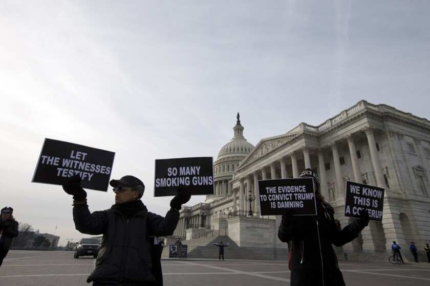 Demonstrators hold signs outside the U.S. Capitol during the impeachment trial of President Trump.