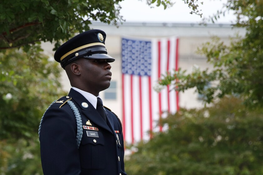 FILE - In this Sept. 11, 2019, file photo, a member of the U.S. Army Old Guard stands on the grounds of the National 9/11 Pentagon Memorial before a ceremony in observance of the 18th anniversary of the September 11th attacks at the Pentagon in Washington. On Sept. 11, 2020, Americans will commemorate 9/11 with tributes that have been altered by coronavirus precautions and woven into the presidential campaign. (AP Photo/Patrick Semansky, File)