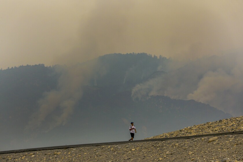 A man walks on Santa Fe Dam as smoke rises from the Bobcat fire on Thursday in the San Gabriel Mountains above Duarte.
