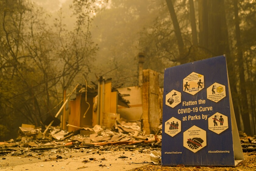 A COVID-19 sign sits in front of a burned structure at Big Basin Redwoods State Park in Boulder Creek, Calif.