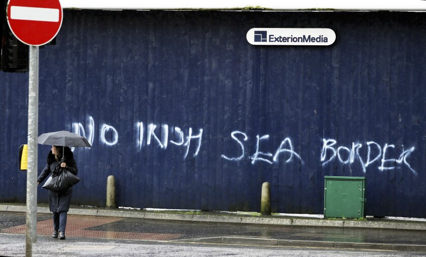 A woman walks past past graffiti with the words 'No Irish Sea Border' in Belfast city centre, Northern Ireland, Wednesday, Feb. 3, 2021. Politicians from Britain, Northern Ireland and the European Union are meeting to defuse post-Brexit trade tensions that have shaken Northern Ireland's delicate political balance. British Cabinet minister Michael Gove, European Commission Vice President Maros Sefcovic and the leaders of Northern Ireland's Catholic-Protestant power-sharing government will hold a video conference to discuss problems that have erupted barely a month after the U.K. made an economic split from the 27-nation EU. (AP Photo/Peter Morrison)