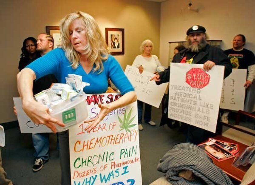 Donna Lambert, a cancer survivor who runs a medical-marijuana collective, brought prescription drugs to the District Attorney's Office on Tuesday to protest her arrest. (K.C. Alfred / Union-Tribune)