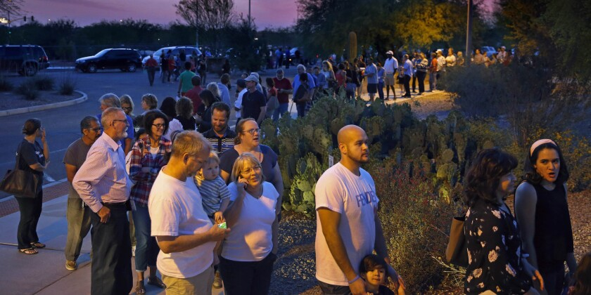 People wait in line to vote on March 22 in Chandler, Ariz. Five polling places in the Phoenix area reportedly still had voters in line after midnight during the state's recent presidential primary.