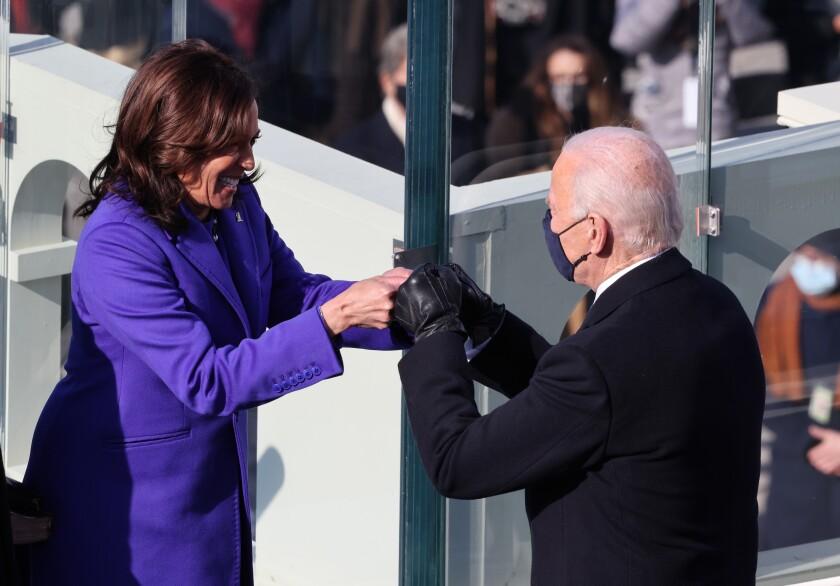 Vice President Kamala Harris and President Joe Biden fist bump during the inauguration