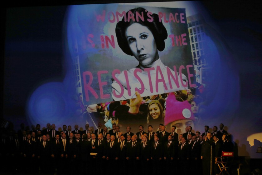 The Gay Men's Chorus of Los Angeles sings during a memorial service as images of Carrie Fisher flash