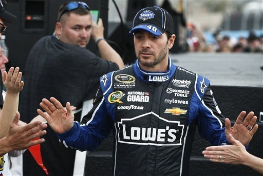 FILE- In this March 3, 2013, file photo, driver Jimmie Johnson gives out high-fives to fans during driver introductions prior to the NASCAR Sprint Cup Series auto race in Avondale, Ariz. Johnson didn't like the way Carl Edwards restarted the race on Sunday, intimating Edwards didn't follow the rule