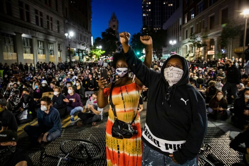 Demonstrators raise their fists during a June 3 protest in Oakland in response to the death of George Floyd.