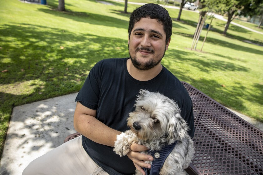 Cudahy resident Ulysses Sandoval pauses on a walk with his dog, Chia, in a park near his home.