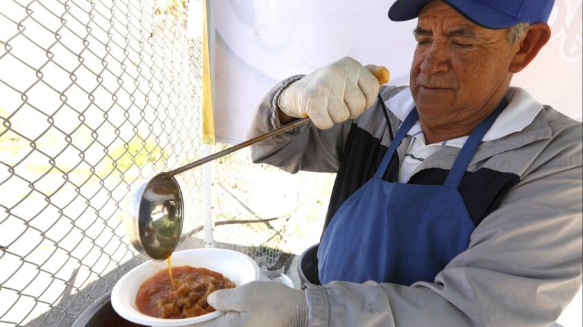 Joel Mendez prepares a bowl of menudo at his Mr. Menudo pop-up stand in Compton. Mendez is a 25-year veteran of the beloved Juanito's in East L.A.