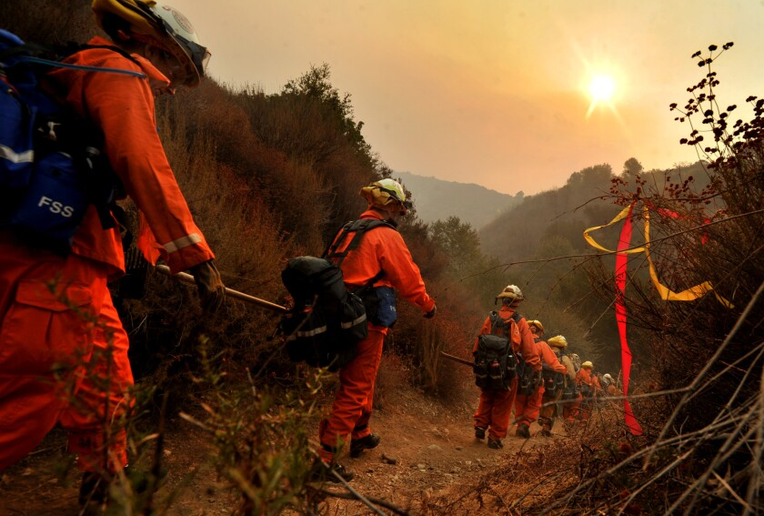 Women wearing orange firefighting suits walk along a dirt trail in hazy air