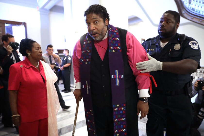 NAACP North Carolina President the Rev. Dr. William Barber, center, is arrested for protesting against new GOP health care legislation in Senate Majority Leader Mitch McConnell's offices on July 13, 2017. Barber has been a vocal critic of President Donald Trump and religious leaders who support him.