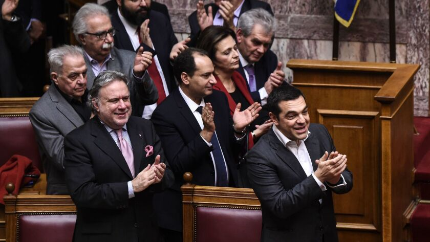 Greece's Prime Minister Alexis Tsipras, right, and Alternate Minister of Foreign Affairs Georgios Katrougalos, left, celebrate following a voting session at the Greek Parliament, in Athens, on Friday.