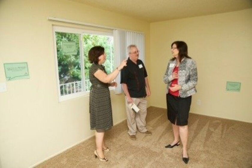Michele St. Bernard, affordable housing project manager for the San Diego Redevelopment Agency, tours a recently upgraded unit at Village Green with Glenn and Linda Roark.