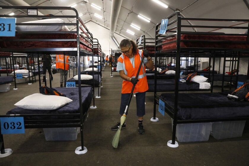 Alpha Project worker Sylvia Saliman sweeps up in San Diego shelter