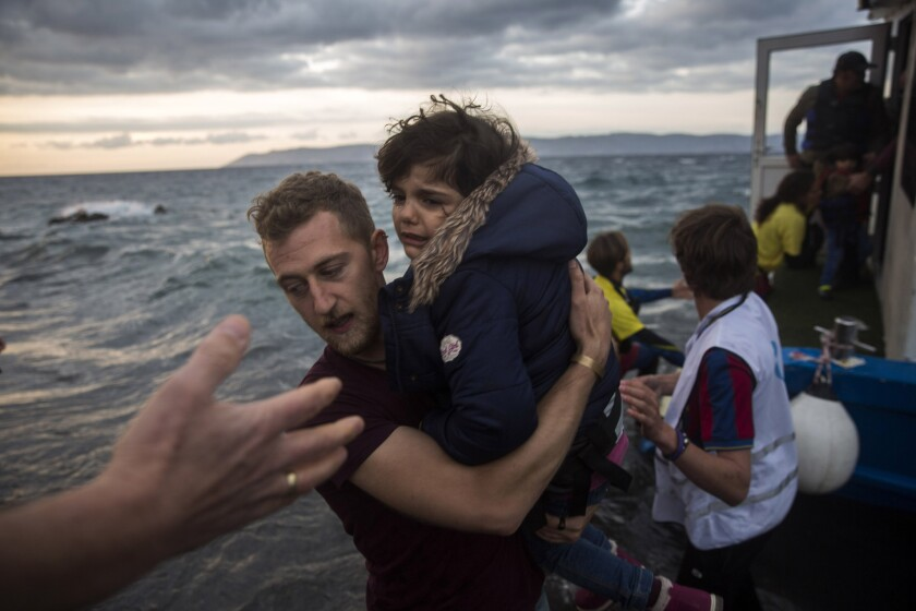 A photographer helps a migrant girl disembark on the Greek island of Lesbos after arriving with around 125 people on a boat from Turkey on Oct. 29.