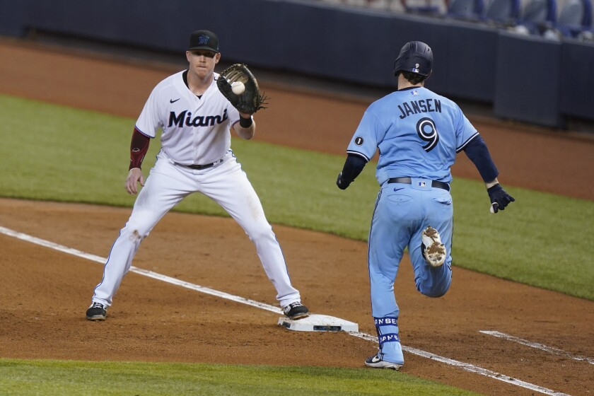Miami Marlins first baseman Garrett Cooper catches the throw to put out Toronto Blue Jays' Danny Jansen (9) at first during the fifth inning of a baseball game Wednesday, Sept. 2, 2020, in Miami. (AP Photo/Wilfredo Lee)