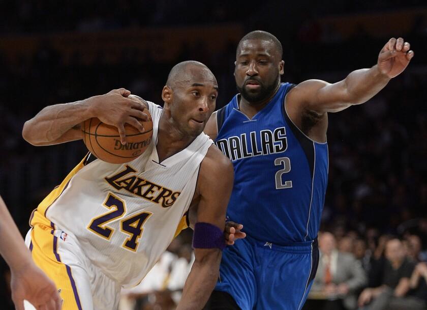Lakers forward Kobe Bryant dribbles past Mavericks guard Raymond Felton in the second half.
