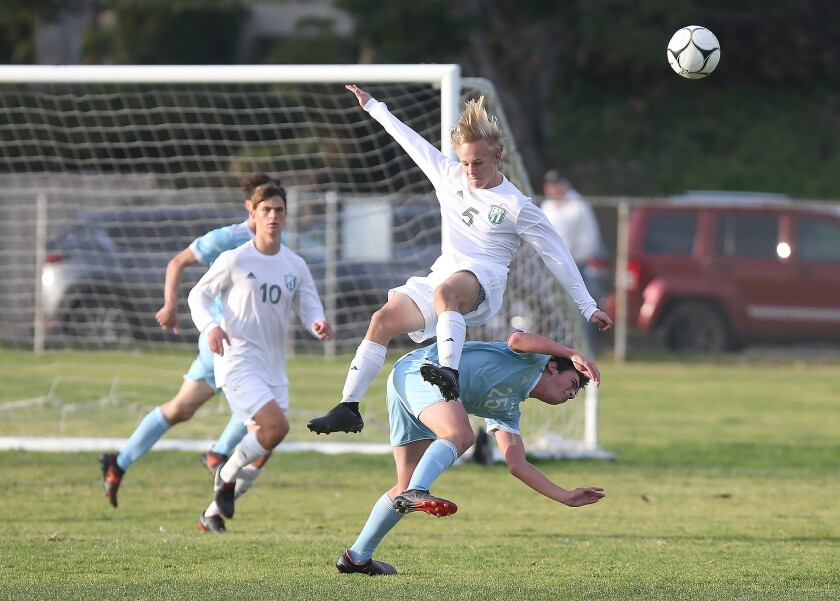 Edison's Marcus Henze (5), shown being upended against Corona del Mar on Jan. 11, scored the eventual game-winning goal for the Chargers on Saturday in the Hawks Invitational semifinals.