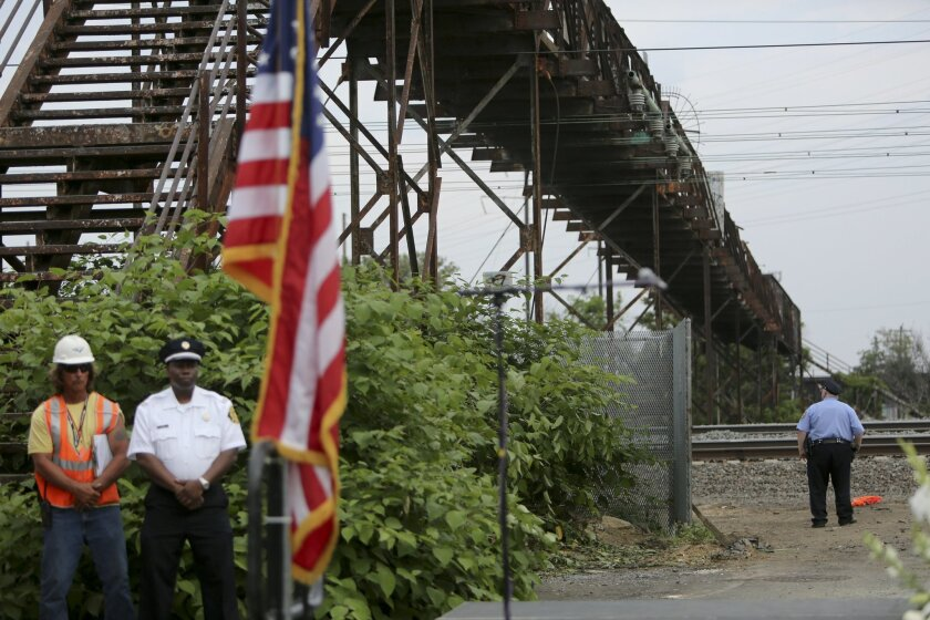 """A police officer looks out over Frankford Junction as officials participate in a service of reflection near the site of an Amtrak train derailment Sunday May 17, 2015, in Philadelphia. The U.S. passenger train operator Amtrak will resume full service in the Northeast Corridor on Monday in """"complete"""