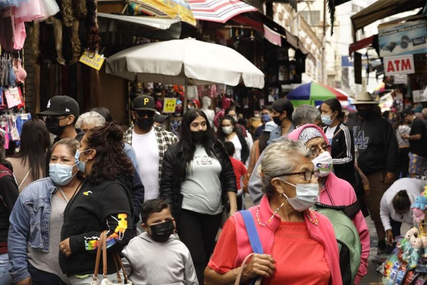 Masked people walk through an outdoor shopping area.