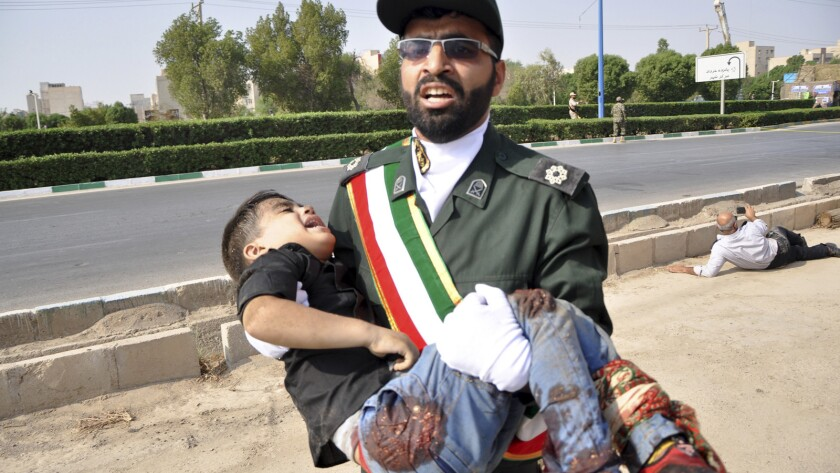 In a photo provided by the Iranian Students' News Agency, a Revolutionary Guard member carries a wounded boy after the shooting at a military parade in Ahvaz, Iran.