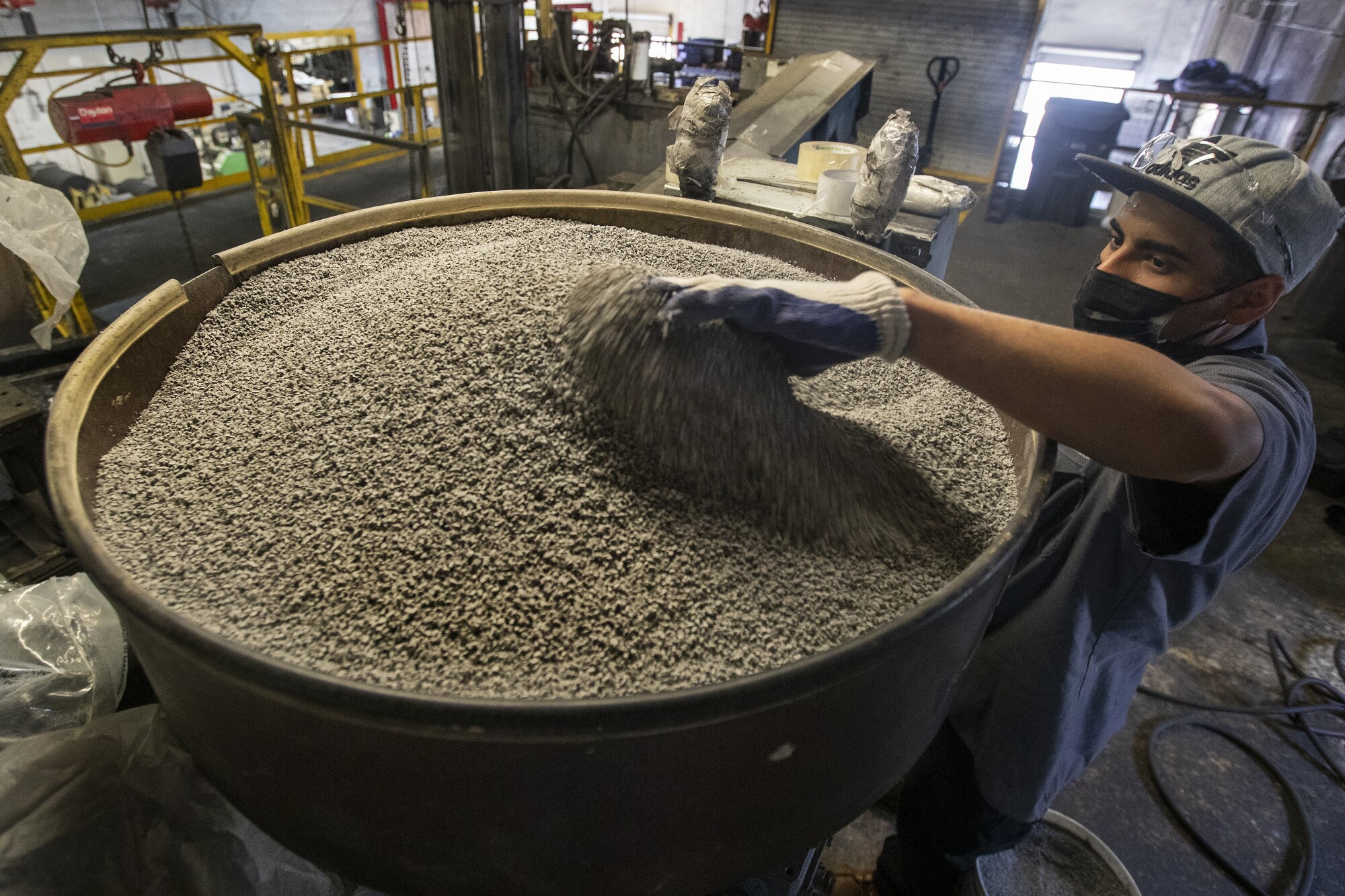 Jonathan Contreras, 28, adds gray coloring, to be mixed in with ground up rubber to make rubber tiles.
