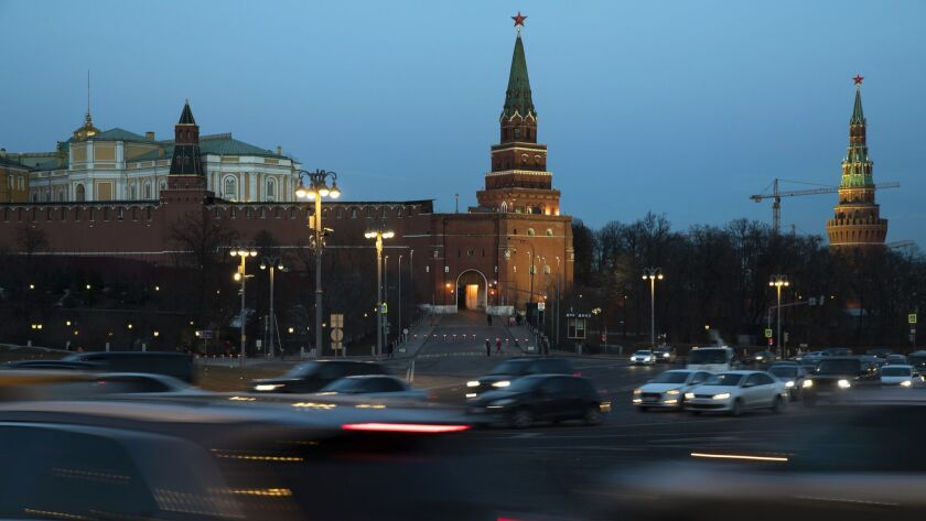 "Cars pass the Kremlin in Moscow, Russia, Monday, March 25, 2019. Russia is reacting with an ""I told"