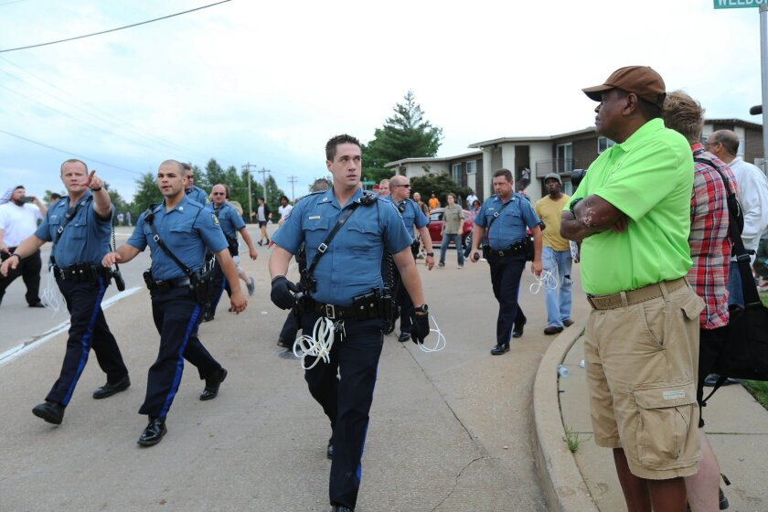 Police walk down the road during an attempt by protesters to shut down Interstate 70 in Berkeley, Mo. on Wednesday, Sept. 10, 2014 near the St. Louis suburb of Ferguson, Mo. where Michael Brown, an unarmed, black 18-year-old was shot and killed by a white police officer on Aug. 9. (AP Photo/St. Louis Post-Dispatch, David Carson)
