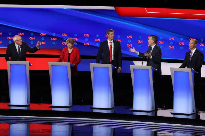 Sen. Bernie Sanders, left, and former Colorado governor John Hickenlooper, second from right, speak while Sen. Elizabeth Warren, former Texas congressman Beto O'Rourke and former Maryland congressman John Delaney look on during the first night of the Democratic presidential debates in Detroit on Tuesday. Twenty Democratic presidential candidates were split into two groups of 10 to take part in the debate sponsored by CNN held over two nights at Detroit's Fox Theatre.