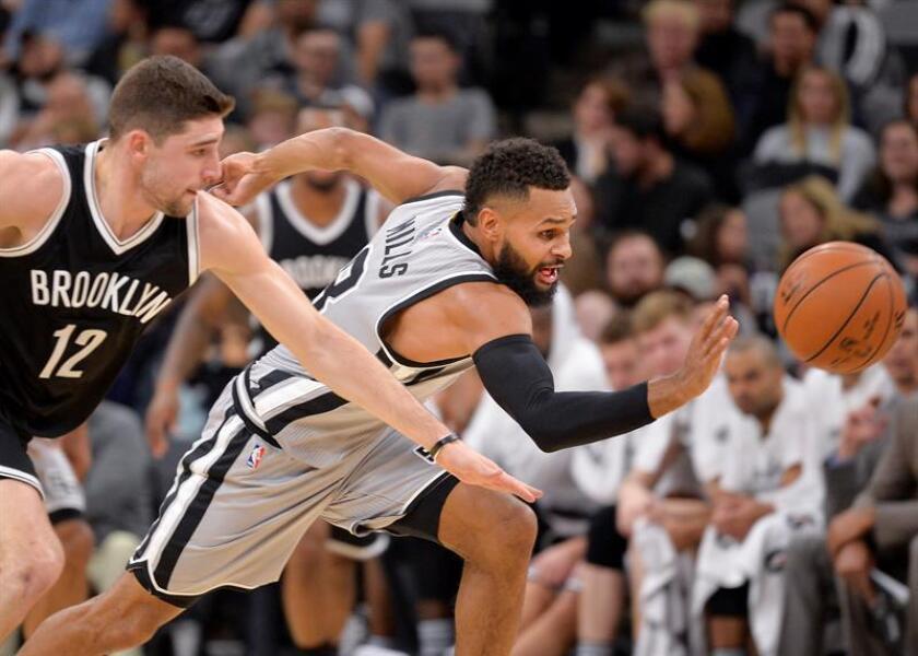 Patty Mills (d) de San Antonio Spurs avanza junto a Trevor Booker (i) Brooklyn Nets durante un juego de la NBA en San Antonio (EE.UU.). EFE