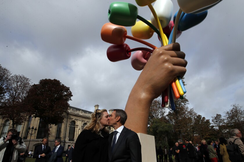 """New York-based artist Jeff Koons poses with his wife Justine Wheeler as he unveiled his much-awaited and controversial sculpture """"Bouquet of Tulips"""" dedicated to the victims of the terrorists attacks, in a garden next to the Champs Elysee near the Petit Palais museum in Paris, Friday, Oct. 4, 2019. (AP Photo/Francois Mori)"""