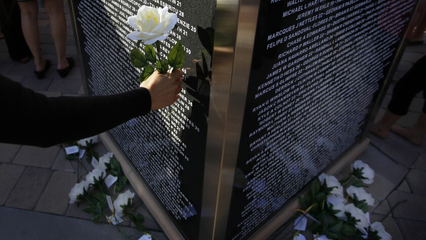 Plastic flowers are placed next to the memorial. Each flower has the name of a fallen solder connec