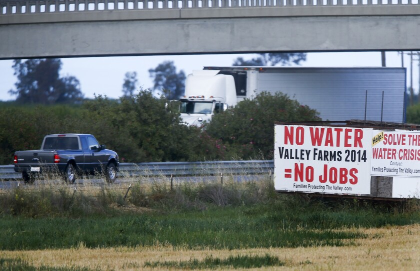 Signs along Highway 99 near Chowchilla connect water cutbacks prompted by the drought to agricultural employment.
