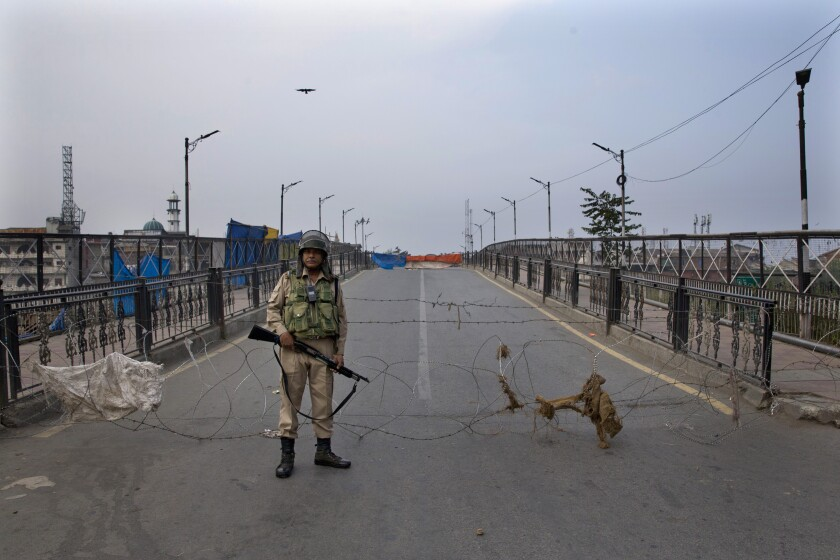 An Indian paramilitary force soldier stands guard near a barbed wire barricade during restrictions in Srinagar Indian controlled Kashmir, Friday, Sept. 27, 2019. Residents in Indian-controlled Kashmir waited anxiously as Indian and Pakistani leaders were scheduled to speak at the U.N. General Assembly later Friday. (AP Photo/ Dar Yasin)