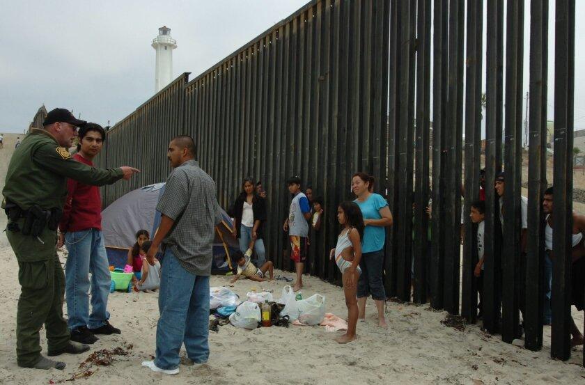Fotografía de archivo, donde se muestra a un agente  de la Patrulla Fronteriza de Estados Unidos discutiendo con migrantes. Se calcula que en Estados Unidos hay unos 11 millones de inmigrantes mexicanos, de los cuales 6,5 son indocumentados, y de éstos alrededor de 30 % (1,95 millones) no tienen ac