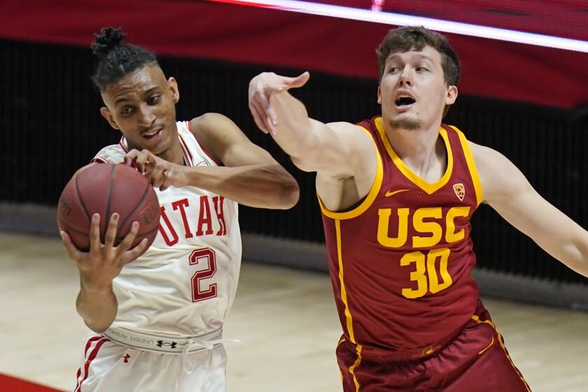 Utah guard Ian Martinez (2) pulls down a rebound as Southern California guard Noah Baumann.